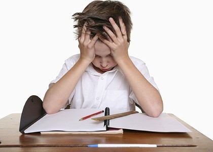 Child holding his head in his hands looking over a book
