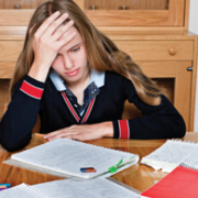 girl holding her head looking at papers