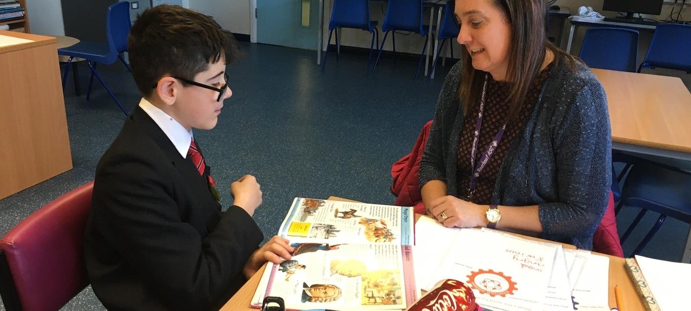 Lynn and a pupil sat at a table looking at a book