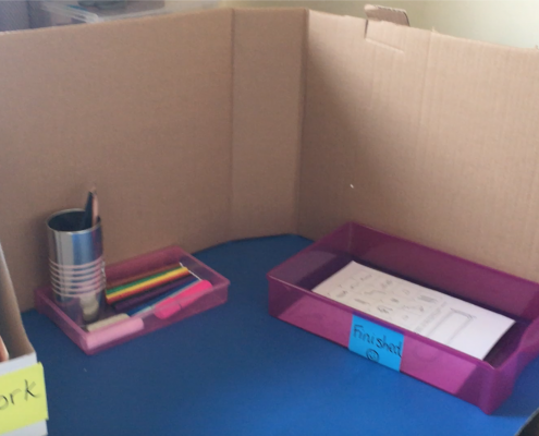 A cardboard screen with trays to put work to do and finished work in