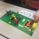 child's hand over a lego model with visual pictures showing what social skills they are working on