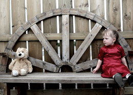 A young girl in a red dress sitting on the right of a long bench with a teddy at the opposite side of the bench.