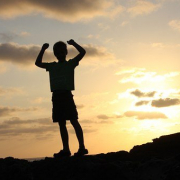 a boy in silhouette holding his arms up in celebration