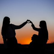 silhouette of two girls putting their hands together in a heart shape
