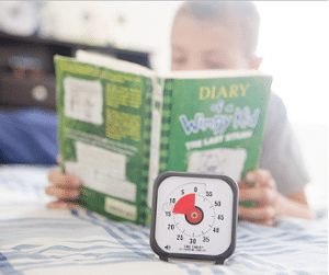 child reading a book with a timer showing 10 minutes.